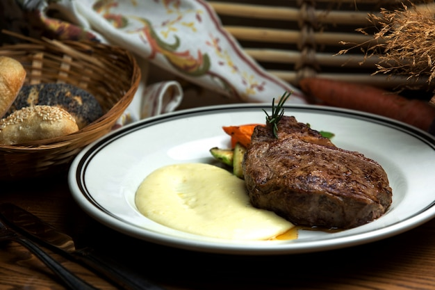 Well-done steak with mashed potatoes and fried vegetables Free Photo