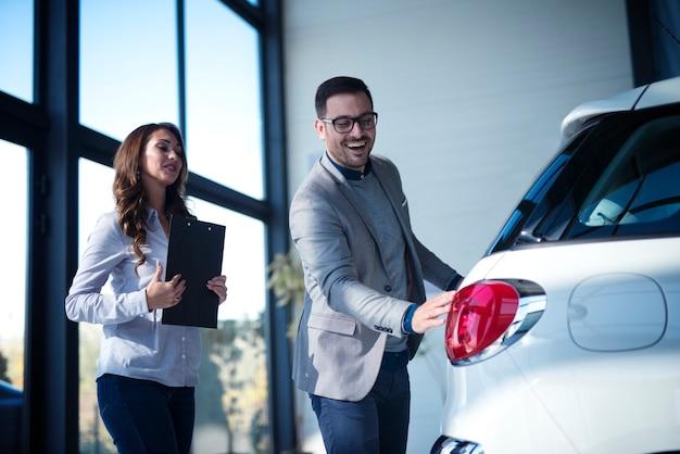 Uomo d'affari ben vestito che acquista una nuova auto mentre il venditore presenta un nuovo veicolo al cliente Foto Gratuite