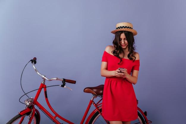 紫の壁に身なりのよい巻き毛の女の子のテキストメッセージメッセージ。自転車の近くに立って、電話の画面を見ている白人のスタイリッシュな女性。 無料写真