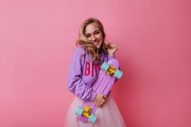 Signora ben vestita con skateboard sorridente su sfondo rosa. ispirata ragazza caucasica con capelli biondi che tiene longboard. Foto Gratuite