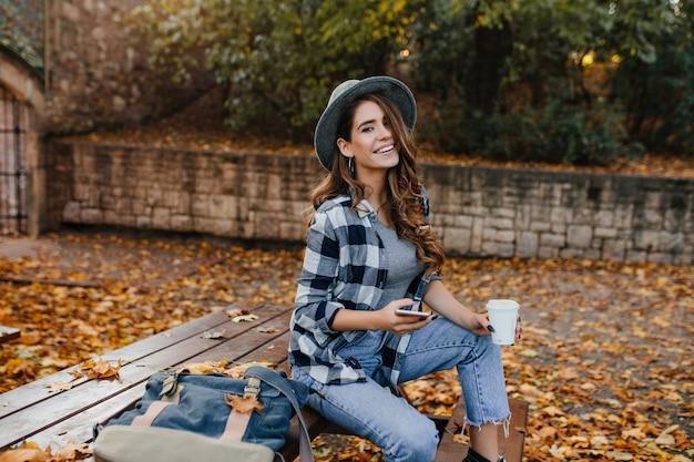 10月の日に公園に座って自然の景色を楽しんでいる薄茶色の髪の身なりのよい笑う女性 無料写真