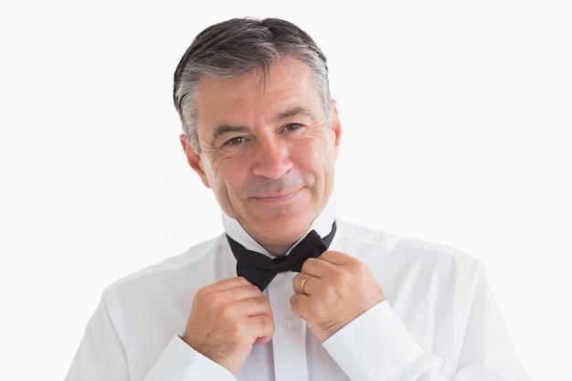 Well-dressed man adjusting his bow tie Premium Photo