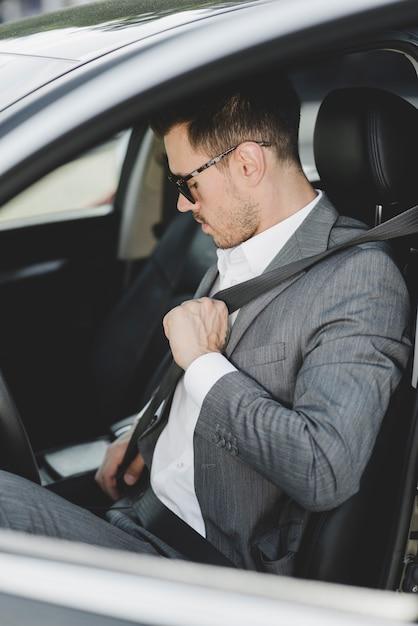 車で安全ベルトを結ぶ服を着た若い男 無料写真