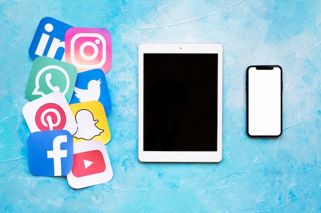 Well-known social media brands printed on paper arranged near digital tablet and smartphone Free Photo