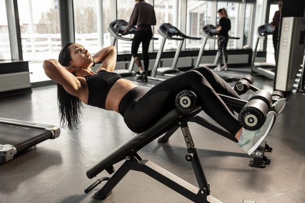 Велнес. молодая мускулистая кавказская женщина упражнениями в тренажерном зале с оборудованием. спортивная (ый) женская модель делает упражнения abs, тренирует верхнюю часть тела, живот. велнес, здоровый образ жизни, бодибилдинг. Бесплатные Фотографии