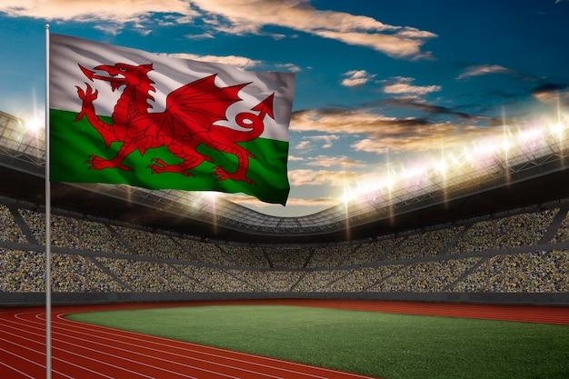 Валлийский флаг перед легкоатлетическим стадионом с болельщиками. Бесплатные Фотографии