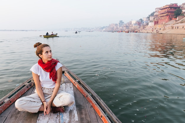 Western woman on a boat exploring the river ganges Free Photo