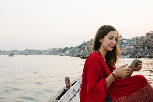 Western woman on a boat texting from the river ganges Free Photo