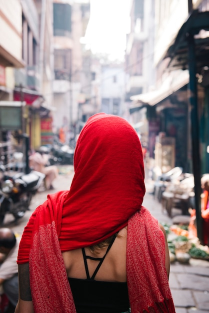 Western woman covered in a red scarf exploring varanasi Free Photo