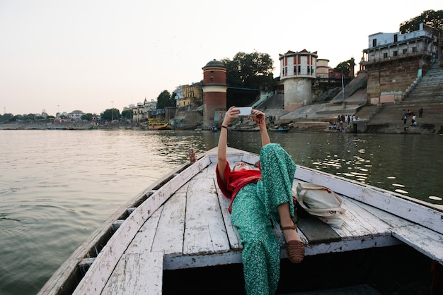 Western woman lying on a boat taking selfies in varanasi Free Photo