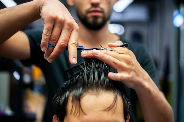 Wet hair getting a haircut in a barber shop Free Photo