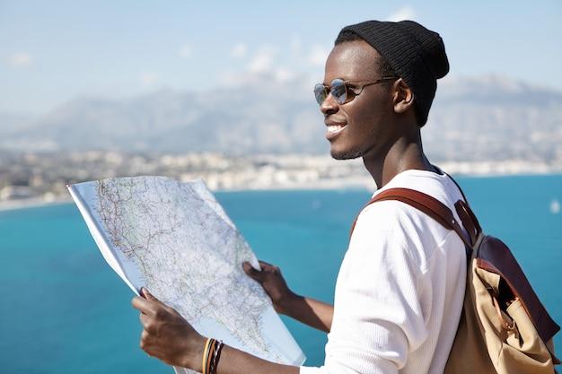 なんて美しい風景でしょう!旅行中に青い海の上にある見晴らしの良い場所に立って周囲を研究しながら、紙の地図を使って幸せな興奮しているアフロアメリカンのバックパッカー。旅行と冒険 無料写真