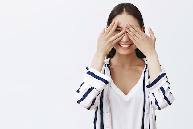 Cosa mi stai nascondendo. ritratto di donna affascinante giocosa incuriosita in camicetta a righe, che copre gli occhi con i palmi delle mani e sbircia tra le dita, sorridendo ampiamente, in attesa di sorpresa Foto Gratuite