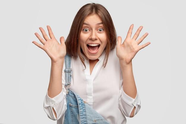 なんて素晴らしい驚きでしょう。大喜びの幸せな女性は手のひらを広げ、広く笑顔 無料写真