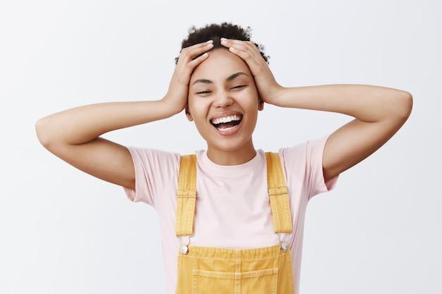 Какое прекрасное время быть живым. портрет беззаботной и радостной привлекательной молодой афро-американской женщины в желтом комбинезоне, трогающей волосы и широко улыбающейся, чувствуя, что начались счастливые каникулы Бесплатные Фотографии