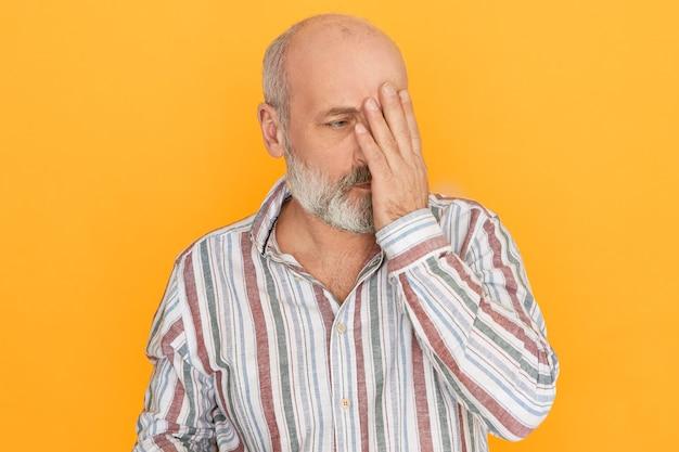 私が何をした。手で顔を覆って、後悔する表情を恥じている白頭ワシの悲しげな不幸な年配の男性の肖像画。 無料写真