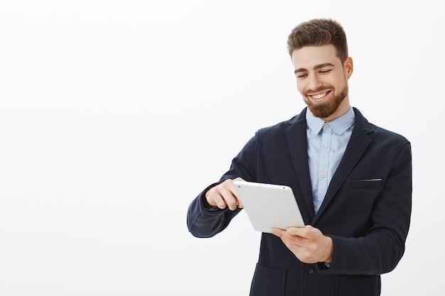 Che piacere guardare un conto in banca pieno di soldi. felice uomo d'affari bello e di successo con la barba e l'acconciatura ordinata in vestito che tiene compressa digitale sorridente soddisfatto guardando lo schermo del dispositivo Foto Gratuite