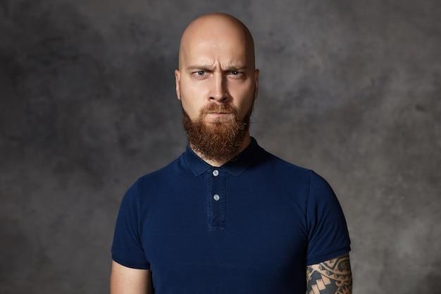 В чем твоя проблема? картина недружелюбного разъяренного молодого бородатого мачо с бритой головой, хмурящегося и преследующего губы, который злится на что-то, его глаза полны ярости, возмущения и гнева Бесплатные Фотографии