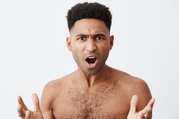 一体何ですか。彼のお気に入りのサッカーチームが試合に負けたとき、混乱した表情で手を広げて服のない巻き毛の美しい黒肌の男のクローズアップ 無料写真