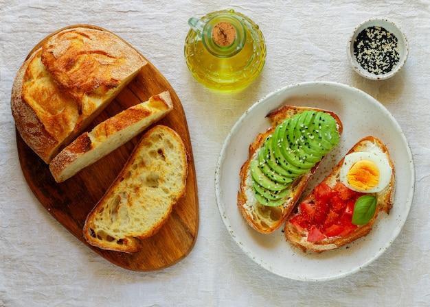 Бутерброды из пшеничного хлеба с авокадо, яйцом, помидором Premium Фотографии