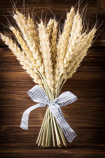 Пучок пшеницы с голубой лентой на деревянном фоне. Premium Фотографии