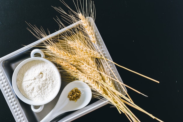 Wheat ears and flour on black background Premium Photo