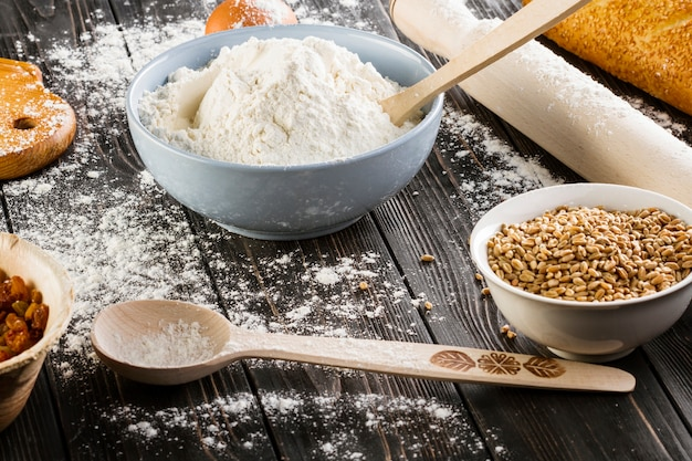Wheat grains and flour in the bowl on the wooden table Free Photo
