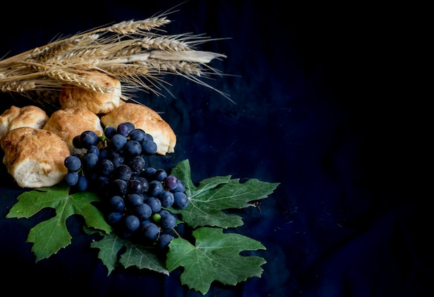 Wheat grapes bread and crown of thorns on black background Premium Photo