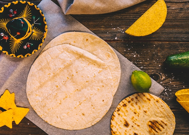 Wheat mexican tortilla; tasty nachos and lemons on wooden table with mexican hat Free Photo