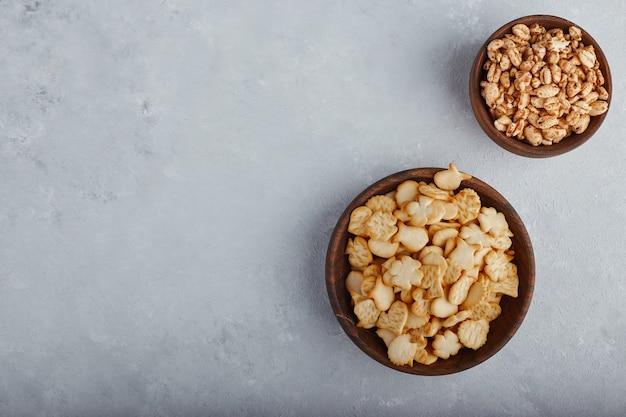 Popcorn e cracker di grano in una ciotola di legno sulla superficie di pietra, vista dall'alto. Foto Gratuite