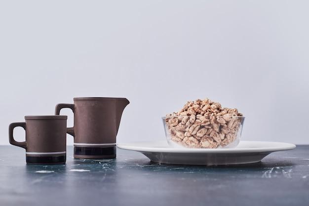 Popcorn di grano nella tazza di vetro in un piatto bianco con una tazza e un bollitore. Foto Gratuite