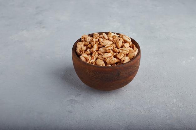 中央の石の背景に木製のボウルに小麦ポップコーン。 無料写真