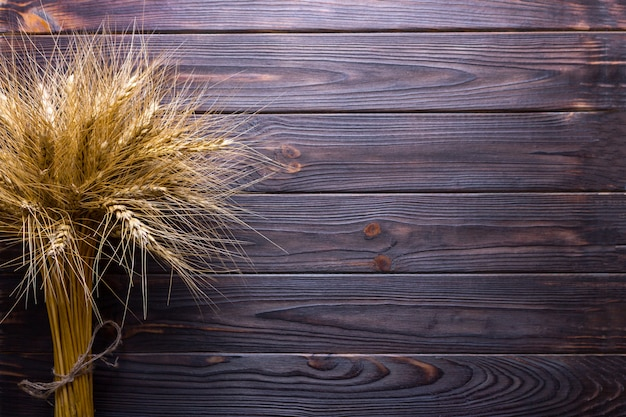 Wheat stems, on wooden background harvest concept Premium Photo