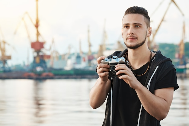 When hobby becomes beloved work. portrait of dreamy creative young guy with beard holding camera and looking aside with thoughtful pleased expression, taking photos of harbour and sea while walking Free Photo