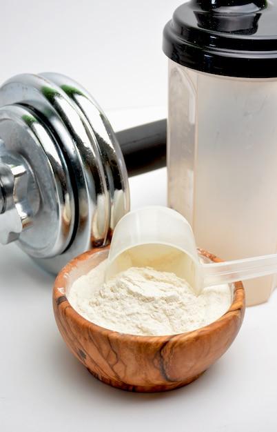 Whey protein taste vanilla with dumbbell Premium Photo