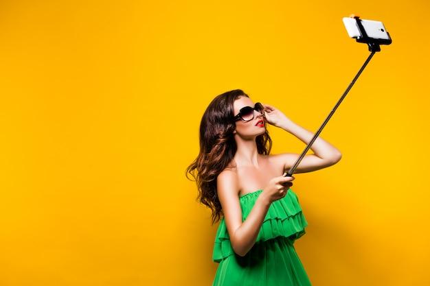 Портрет молодой модели в зеленом платье и солнцезащитные очки, позирует whi Premium Фотографии