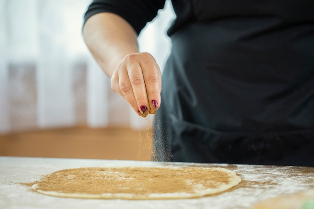 While making homemade cookies, a woman's hand sprinkles cinnamon dough Premium Photo