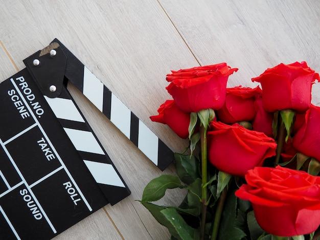 茶色の木製のテーブルwhis赤いバラのビンテージクラシックカチンコ。 Premium写真