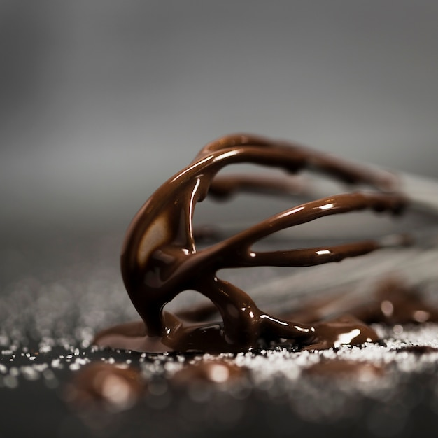 Whisk filled with melted chocolate close-up Free Photo