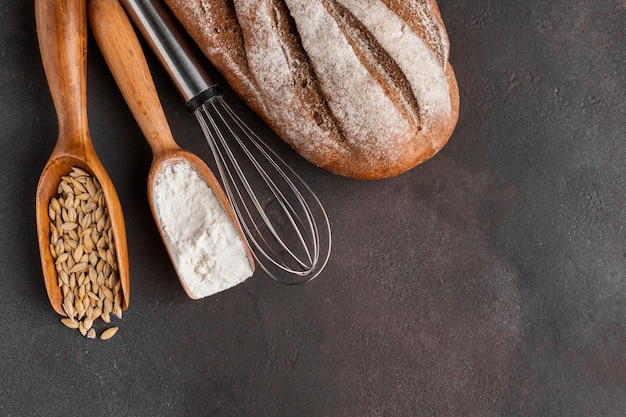 Whisk and wooden spoons with flour and seeds Free Photo