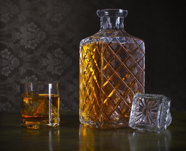 Whiskey  in bottle and glass with ice Premium Photo