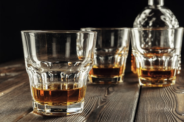 Whiskey glass and bottle on the old wooden table Premium Photo