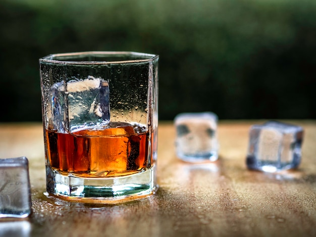 Whiskey glass with nature background Premium Photo