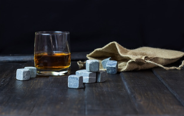 Whiskey in a glass with stones for cooling drinks on a wooden table Premium Photo