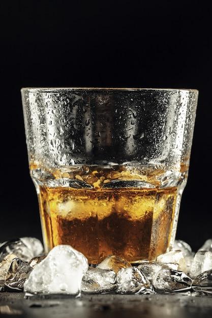 Whiskey and ice on dark background Premium Photo