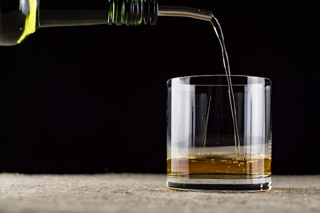 Whiskey is poured into a glass Premium Photo