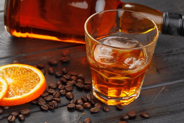 Whiskey or liqueur, coffee beans and orange cut on wooden. Premium Photo