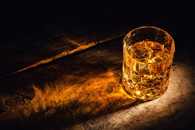 Whiskey with ice cubes on wooden background Premium Photo