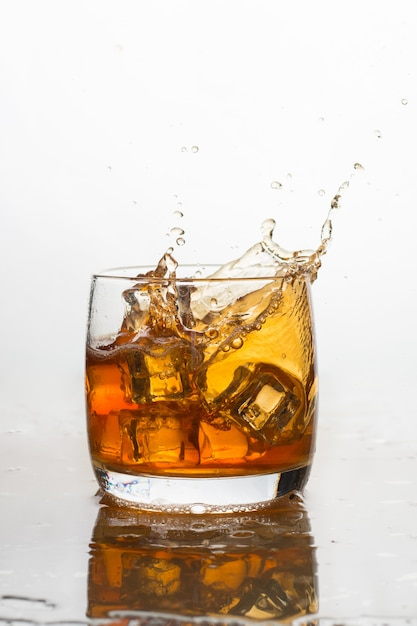 Whiskey with ice in a glass with splashes Premium Photo