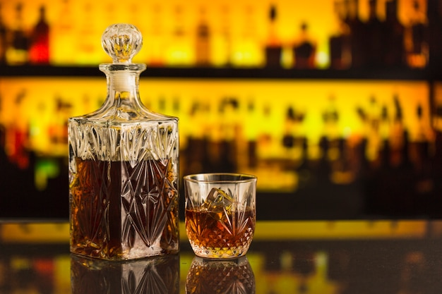 Whisky bottle and glass on bar counter Free Photo